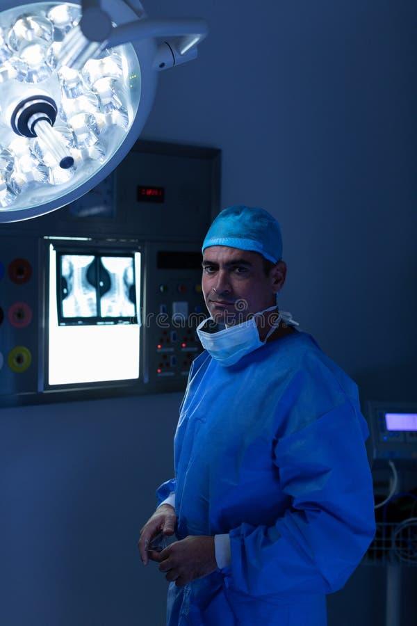 Mannelijke chirurg die zich in werkende ruimte bij het ziekenhuis bevinden stock afbeeldingen