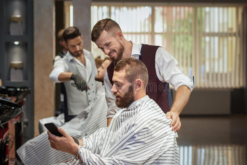 Mannelijke cliënt die kapsel in telefoon in kapperswinkel tonen royalty-vrije stock foto
