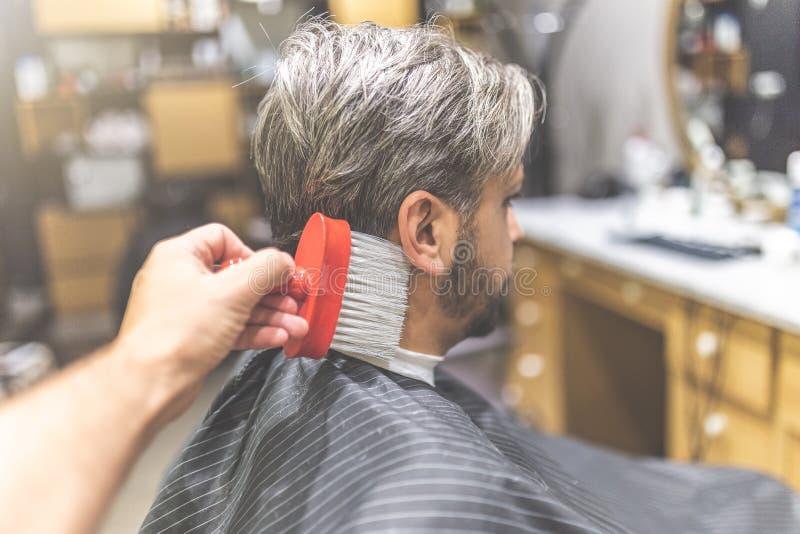 Mannelijke cliënt en kapper schoonmakende hals met borstel stock afbeeldingen