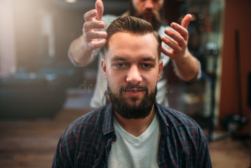 Mannelijke cliënt na het maken van kapsel bij herenkapper stock afbeeldingen
