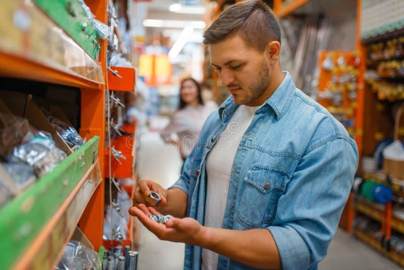 Mannelijke consument die noten kiest in de hardwarewinkel royalty-vrije stock foto