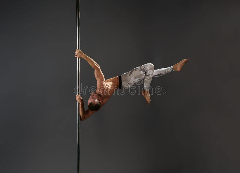 Mannelijke danser bij pyloon in de studio van de pooldans stock foto