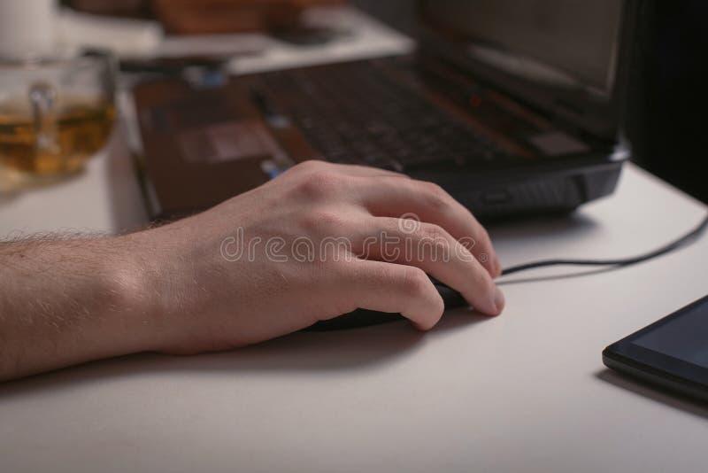 Mannelijke de computermuis van de handholding met laptop toetsenbord op de achtergrond stock foto