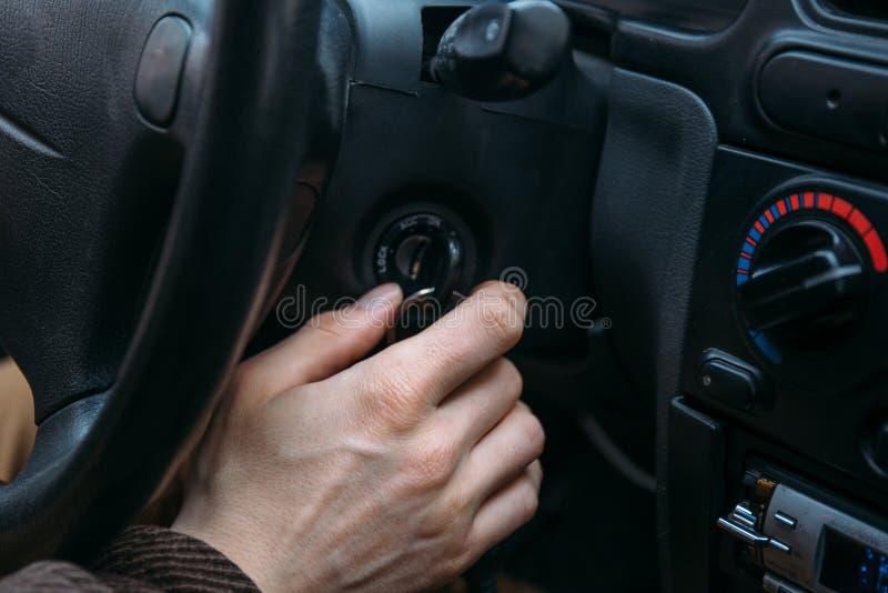 Mannelijke de tussenvoegselssleutel van de bestuurdershand in ontstekingsslot om auto te beginnen royalty-vrije stock fotografie