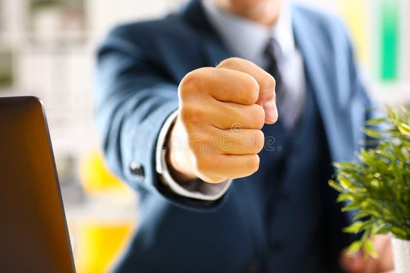 Mannelijke dichtgeklemde vuist in kostuum bij bureauclose-up royalty-vrije stock foto's