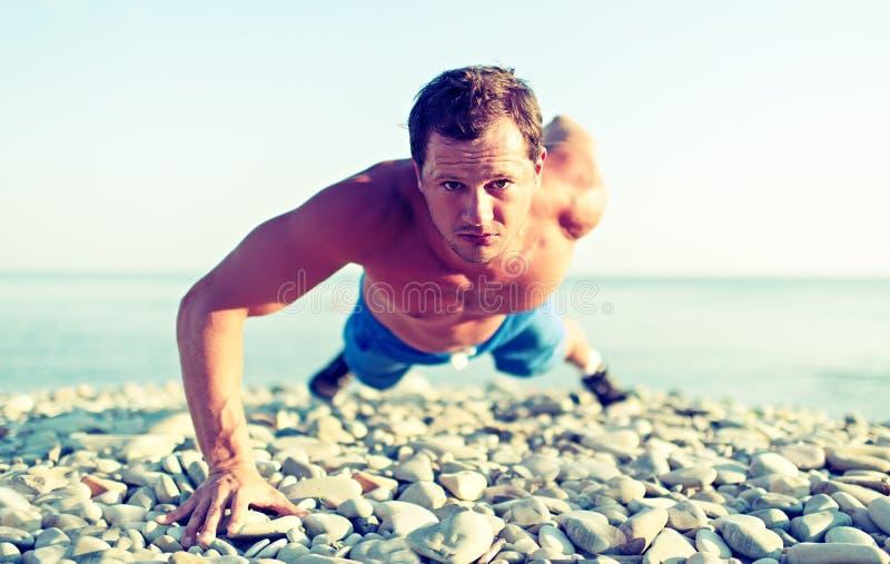 Mannelijke die atletentreinen op aard op het strand worden geduwd stock fotografie