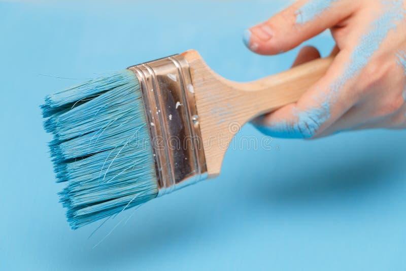 Mannelijke die hand in verf, die een geschilderde verfborstel op een houten oppervlakte houden als achtergrond, met blauwe verf w royalty-vrije stock foto