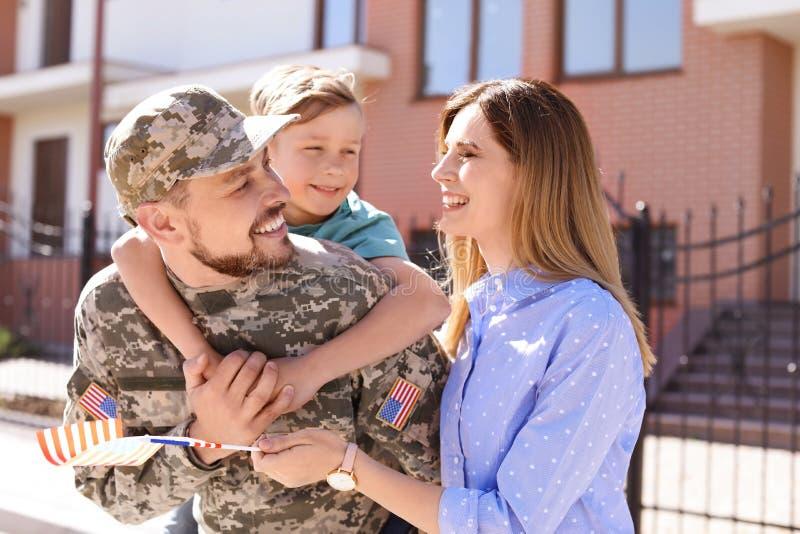 Mannelijke die militair met zijn familie in openlucht wordt herenigd Legerdienst stock afbeeldingen