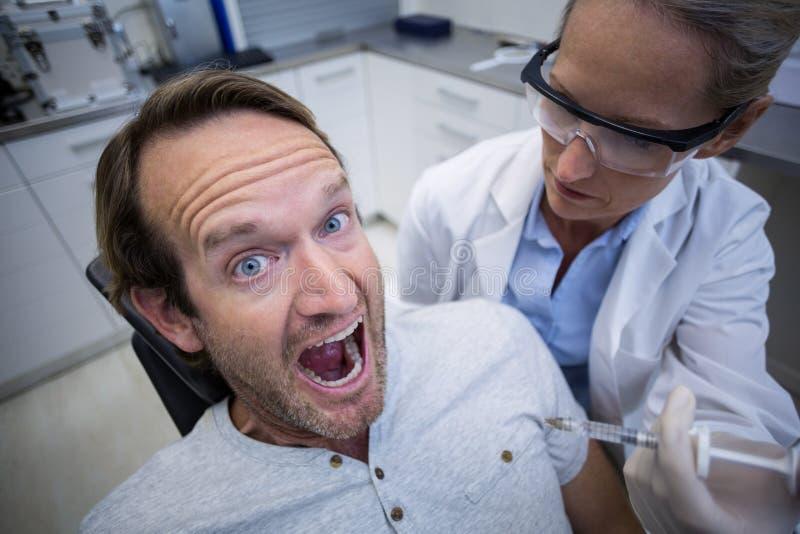 Mannelijke die patiënt tijdens een tandcontrole wordt doen schrikken stock foto's