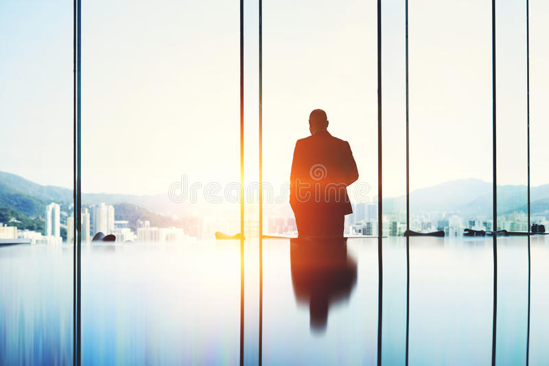 Mannelijke econoom terwijl zich in modern wolkenkrabberbinnenland tegen venster met exemplaarruimte bevindt royalty-vrije stock afbeeldingen