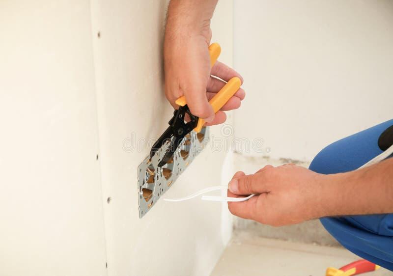Mannelijke elektricien die contactdoos in vlakte, close-up herstellen stock foto