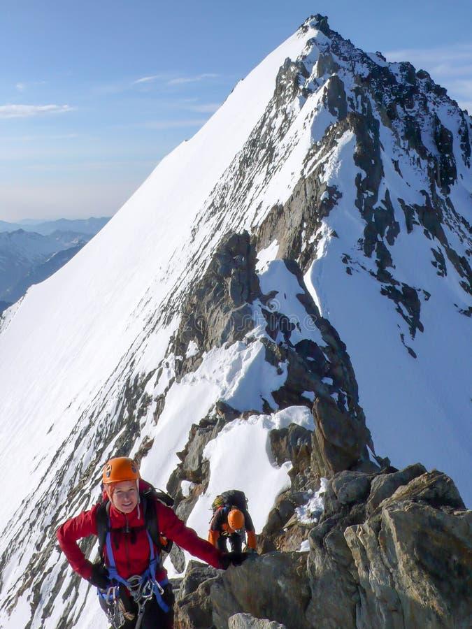 Mannelijke en vrouwelijke alpinist op een blootgestelde rotsachtige toprand op hun manier aan een hoge alpiene bergpiek royalty-vrije stock foto