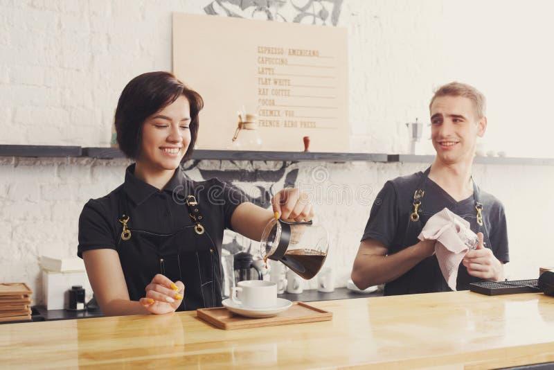Mannelijke en vrouwelijke barmannen die verse koffie brouwen stock afbeeldingen