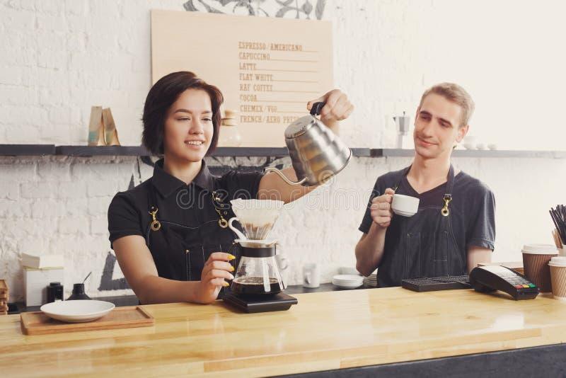 Mannelijke en vrouwelijke barmannen die verse koffie brouwen stock fotografie