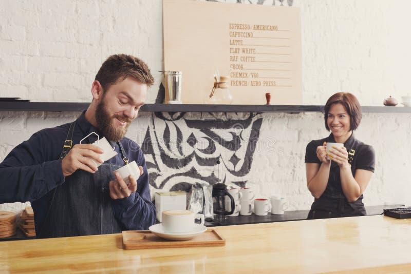 Mannelijke en vrouwelijke barmannen die verse koffie brouwen stock foto