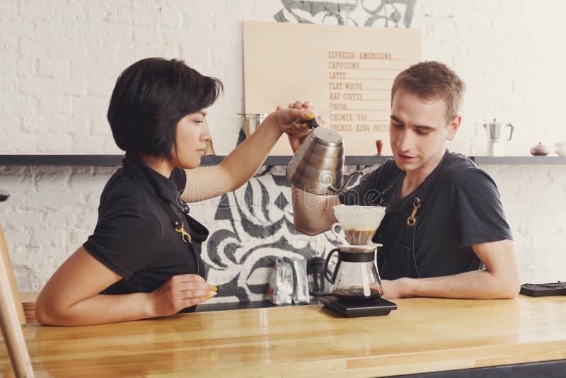 Mannelijke en vrouwelijke barmannen die verse koffie brouwen royalty-vrije stock afbeelding