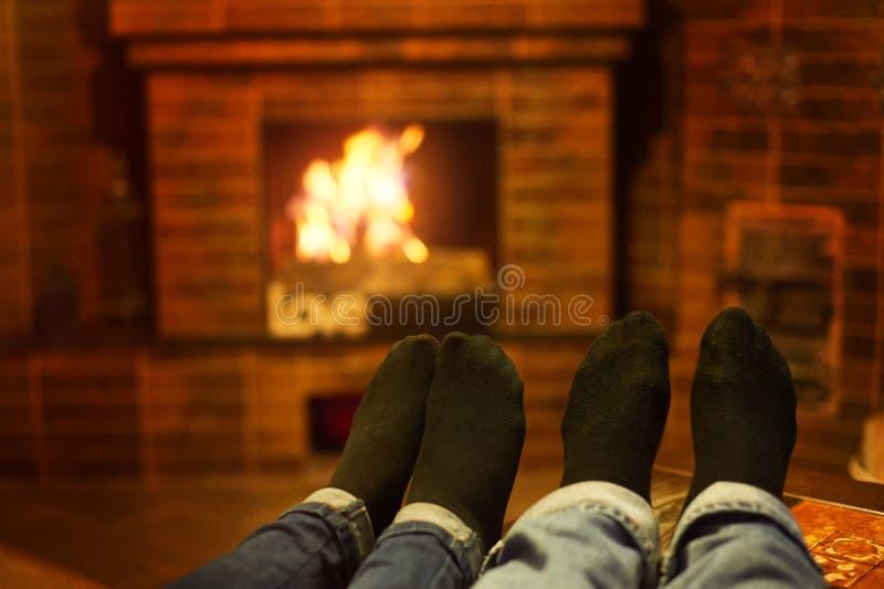 Mannelijke en vrouwelijke benen dichtbij de open haard Het concept van de familie stock fotografie
