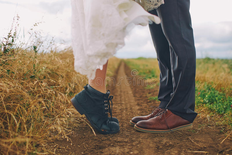Mannelijke en vrouwelijke benen in laarzen op gebied Liefde, kusconcept stock foto's