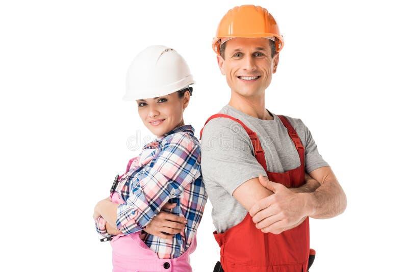 Mannelijke en vrouwelijke bouwers in bouwvakkers en overall stock afbeelding