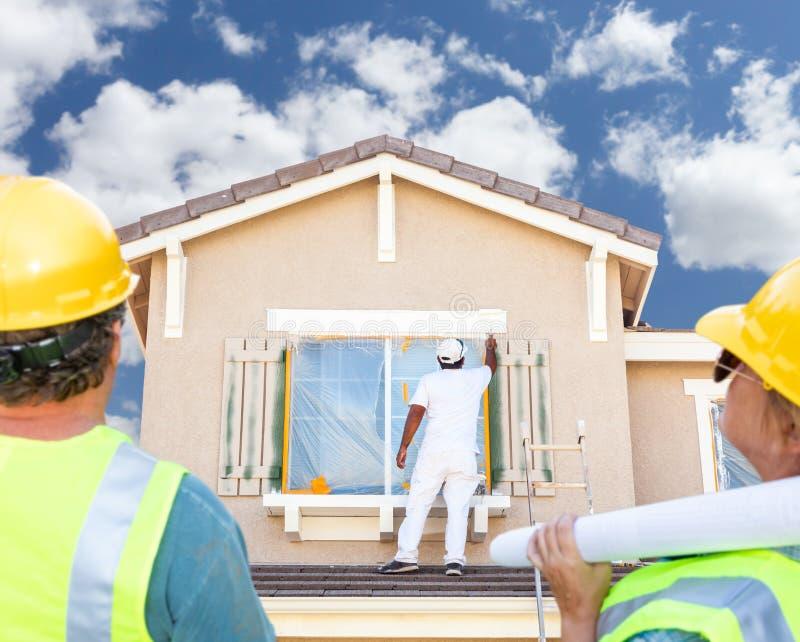 Mannelijke en Vrouwelijke Contractanten die Schilder Painting House overzien stock fotografie
