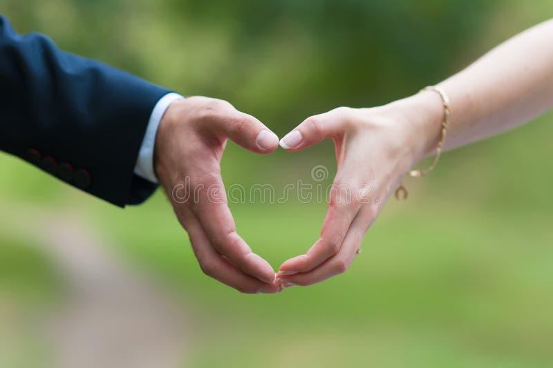 Mannelijke en vrouwelijke die hand in vorm van hart wordt verbonden stock afbeeldingen