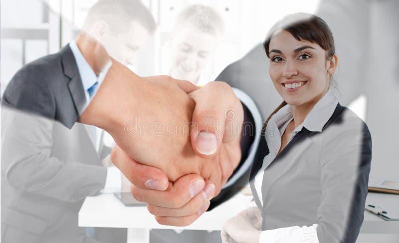 Mannelijke en vrouwelijke handdruk in bureau stock afbeelding