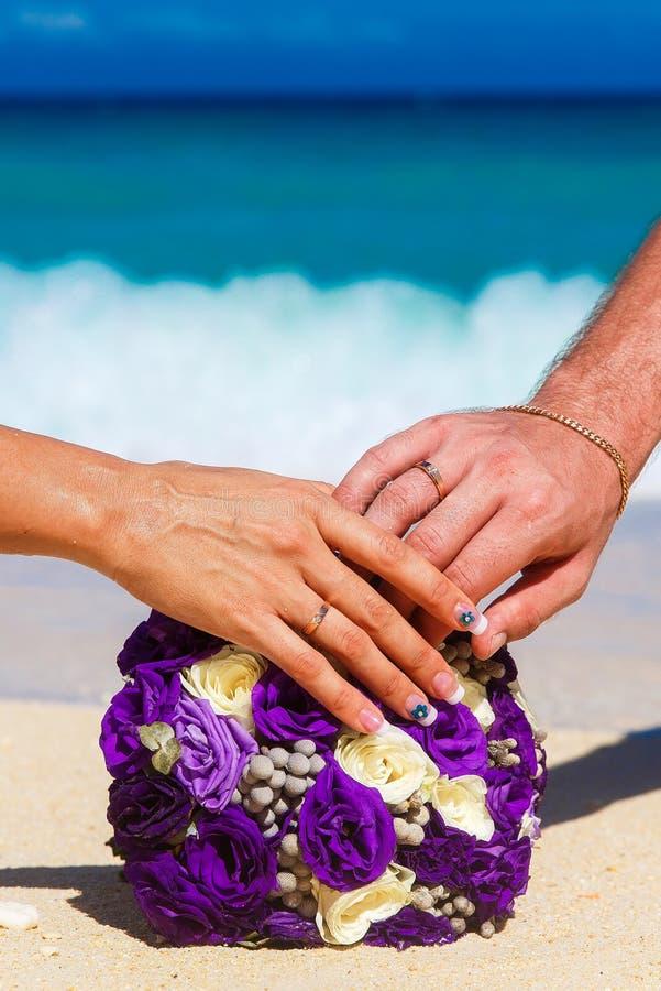 Mannelijke en vrouwelijke handen met het boeket liggend o van het trouwringenhuwelijk stock foto's