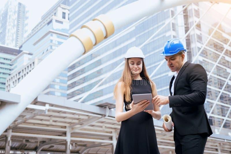 Mannelijke en vrouwelijke industriële ingenieurs een tablet en blauwdrukken houden die werkend en op bouwterrein bespreken royalty-vrije stock afbeeldingen