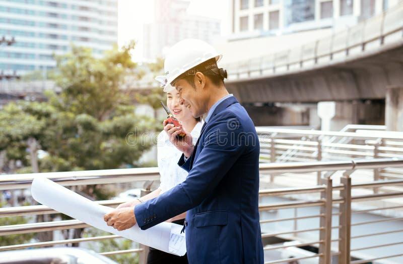 Mannelijke en vrouwelijke industriële ingenieurs een tablet en blauwdrukken houden die werkend en op bouwterrein bespreken royalty-vrije stock foto's