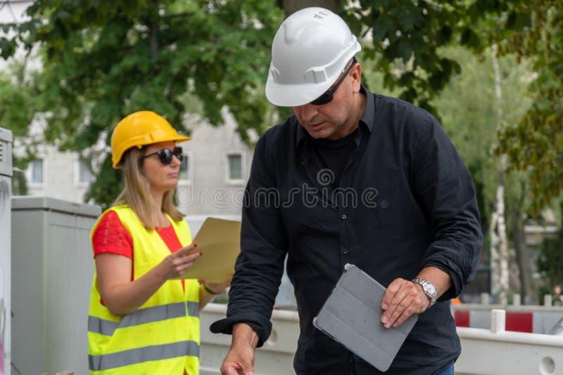 Mannelijke en vrouwelijke ingenieurs aan het werk aangaande bouwwerf stock foto's