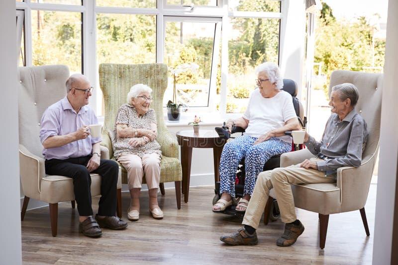 Mannelijke en Vrouwelijke Ingezetenen die als Voorzitter zitten en in Zitkamer van Pensioneringshuis spreken royalty-vrije stock foto
