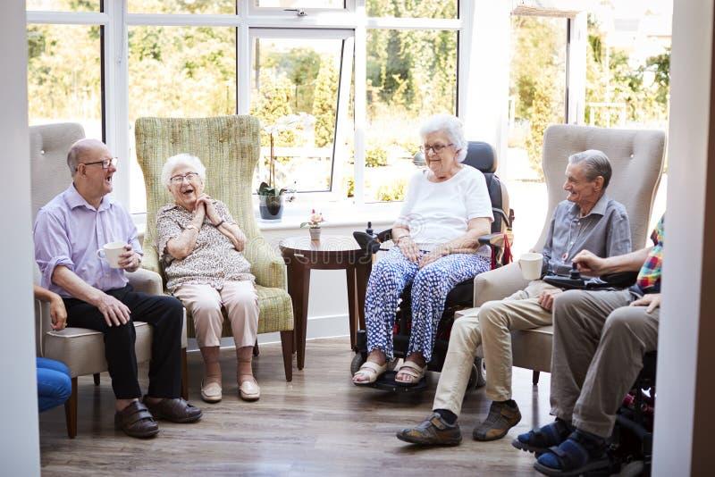 Mannelijke en Vrouwelijke Ingezetenen die als Voorzitter zitten en in Zitkamer van Pensioneringshuis spreken stock foto