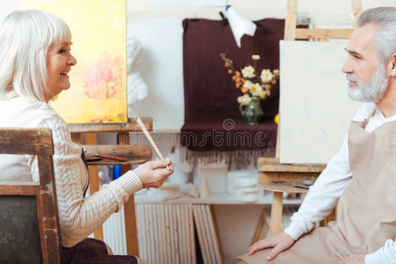 Mannelijke en vrouwelijke kunstenaars die in samen het schilderen van klasse zitten royalty-vrije stock foto