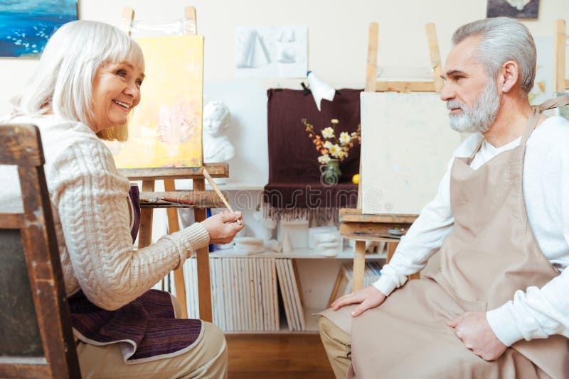 Mannelijke en vrouwelijke kunstenaars die samen schilderen stock afbeeldingen