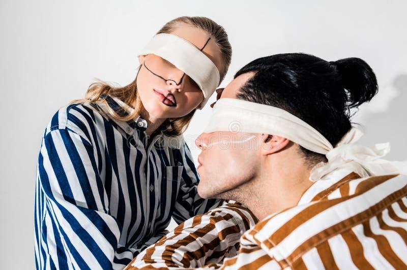 Mannelijke en vrouwelijke modellen die blinddoeken en lijnen op gezicht hebben royalty-vrije stock foto's