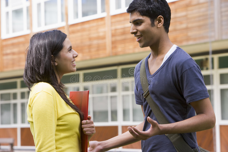 Mannelijke en vrouwelijke studenten die op campus spreken stock foto