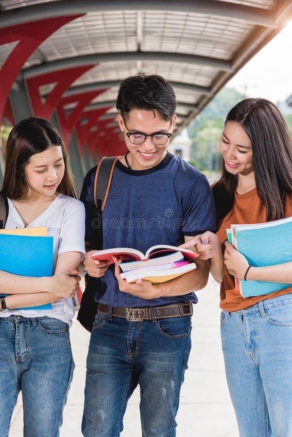 Mannelijke en vrouwelijke studententribune op boeken en laptop computers op campus royalty-vrije stock foto