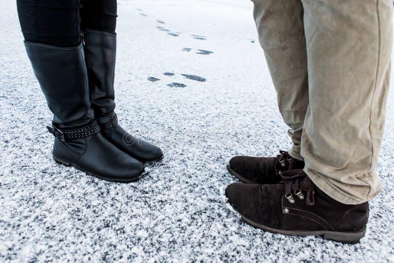 Mannelijke en Vrouwelijke toevallige laarzen die zich op asfalt behandelde zanderige sneeuwoppervlakte bevinden Textplace De koud stock afbeeldingen