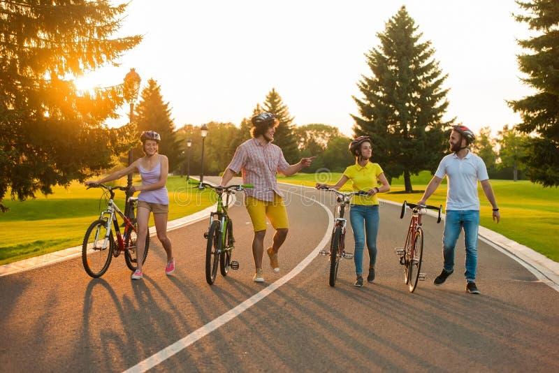 Mannelijke en vrouwelijke vrienden op weg met hun fietsen stock foto's