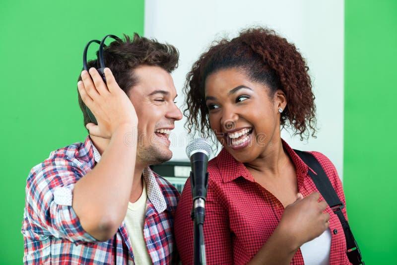 Mannelijke en Vrouwelijke Zangers die terwijl het Bekijken elkaar presteren stock afbeelding