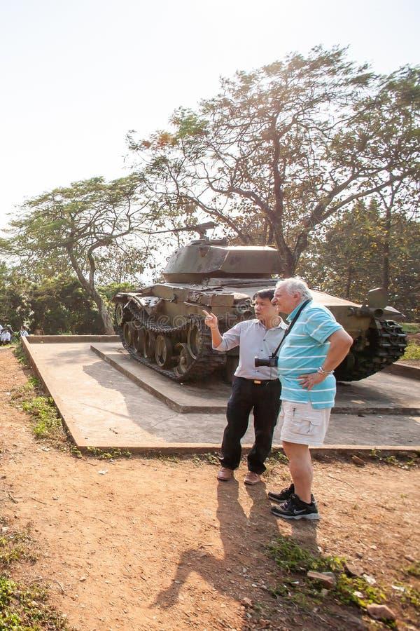Mannelijke Europees luistert aan een Vietnamese gids die over A1-heuvel, het belangrijkste kamp spreken van de Franse kolonisten  royalty-vrije stock afbeelding