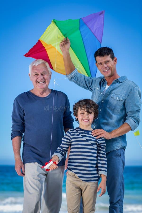 Mannelijke familieleden die met een vlieger spelen stock fotografie