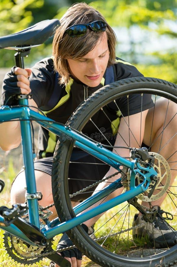 Mannelijke fietser die zijn fiets controleren stock foto's