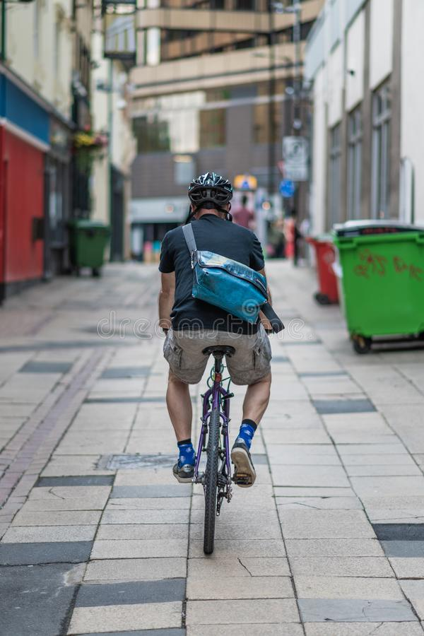 Mannelijke fietser met een helm op ritten door een achtersteeg in Sheffield City Centre royalty-vrije stock afbeeldingen