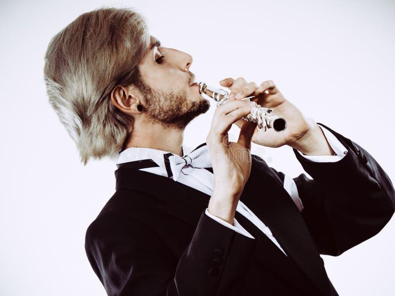 Mannelijke fluitist die de fluit van rokspelen dragen stock afbeelding