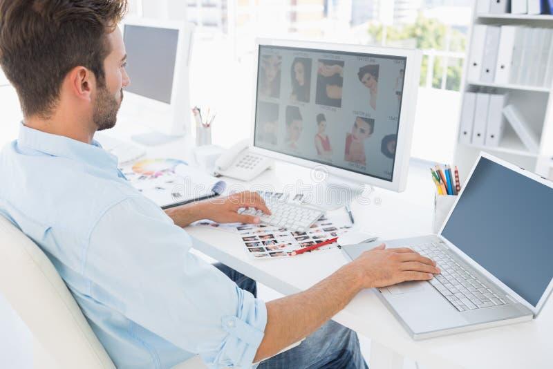 Mannelijke fotoredacteur die aan computer in een helder bureau werken stock foto