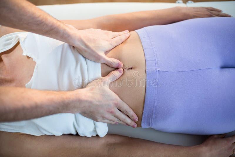 Mannelijke fysiotherapeut die maagmassage geven aan vrouwelijke patiënt stock afbeeldingen