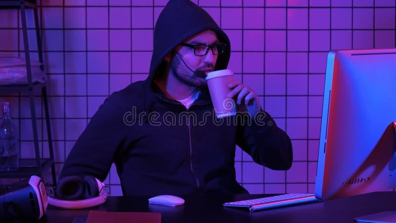 Mannelijke gamer die met een kap op een spel op computer letten stock afbeeldingen