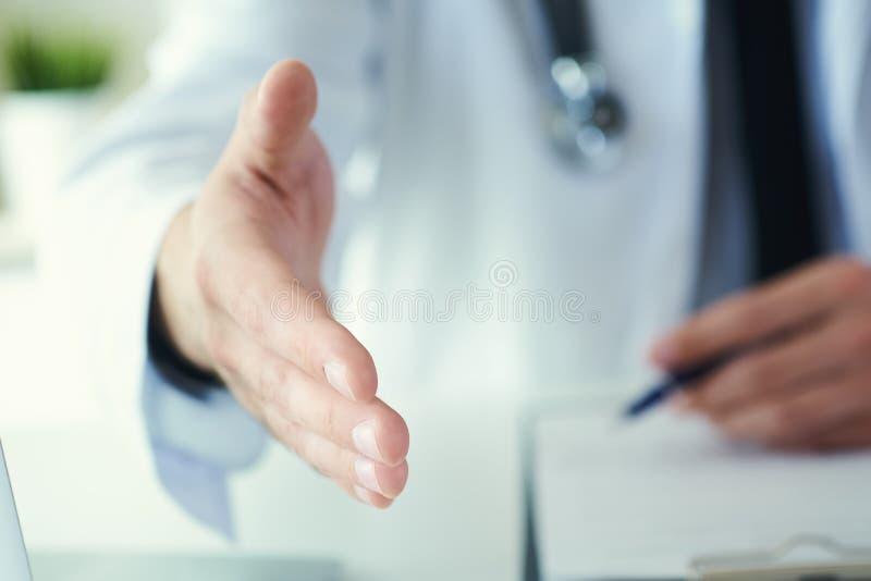 Mannelijke geneeskunde arts die hand aanbieden aan schok in bureauclose-up Het begroeten en het welkom heten gebaar Medische beha royalty-vrije stock afbeelding