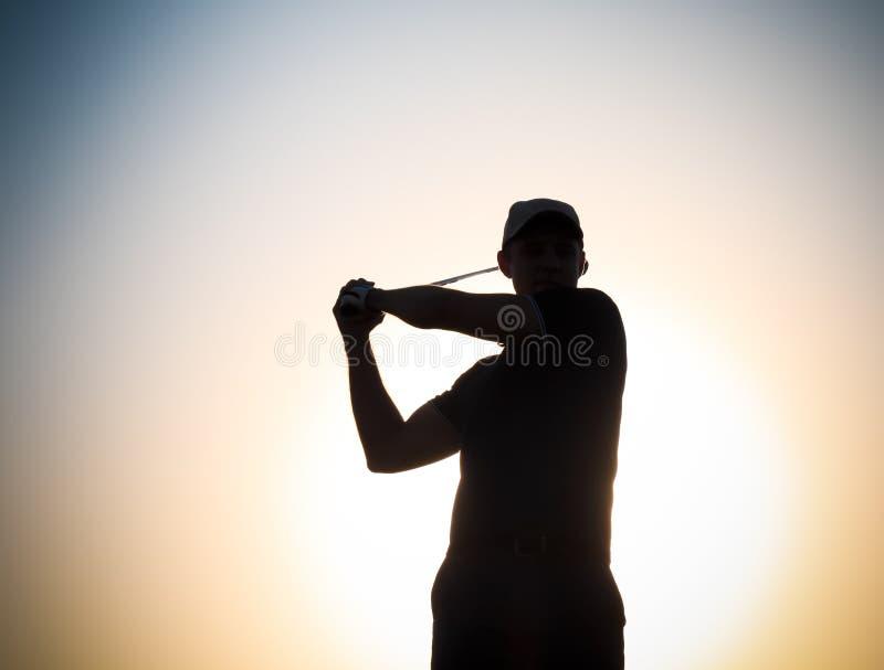 Mannelijke golfspeler bij zonsondergang royalty-vrije stock foto's